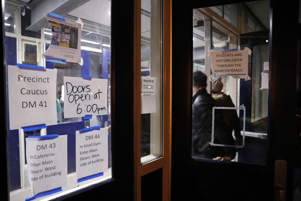 Caucus goers arrive at a caucus at Roosevelt Hight School, Monday, Feb. 3, 2020, in Des Moines, Iowa. (AP Photo/Andrew Harnik)