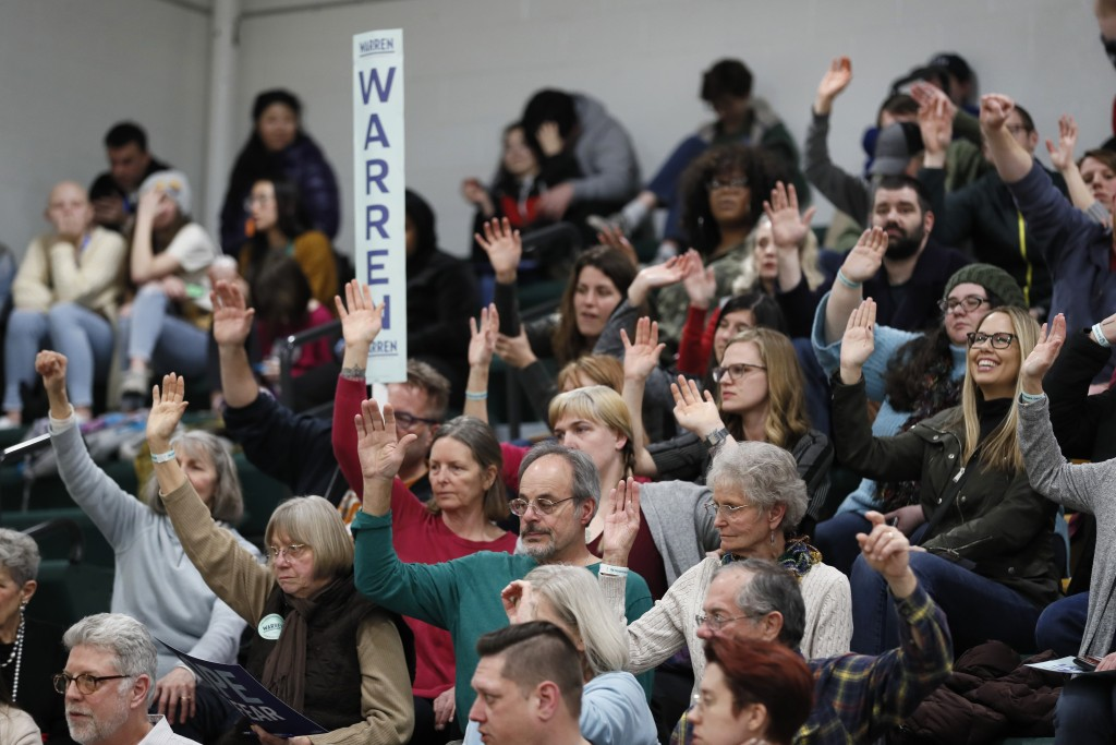 Supporters for Democratic presidential candidate Sen. Elizabeth Warren, D-Mass., raise their hands to be counted during a Democratic party caucus at H...