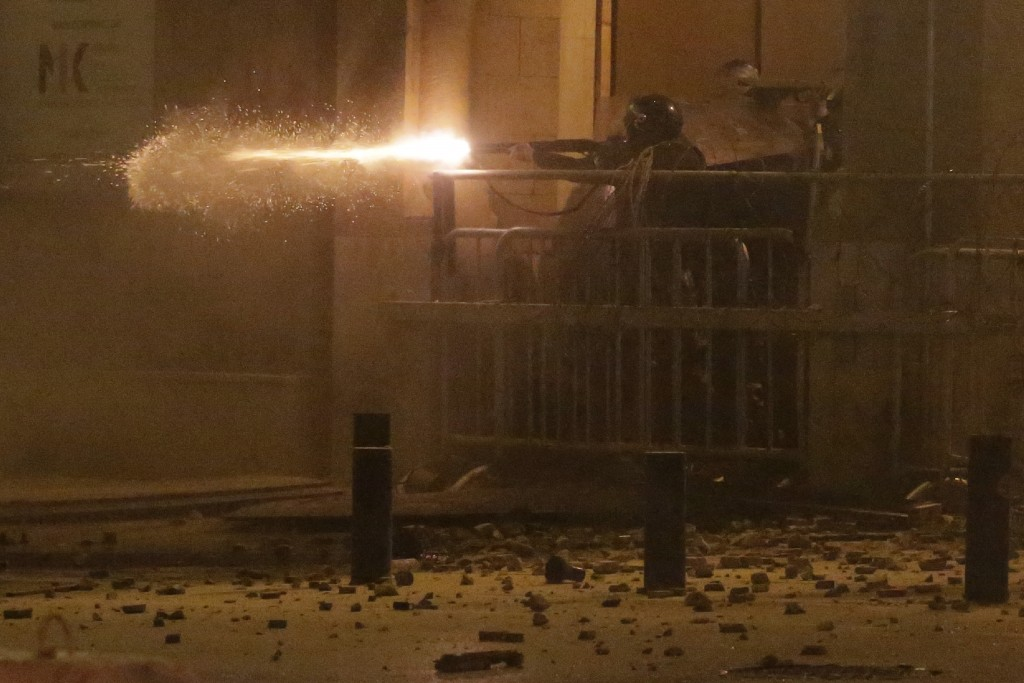 FILE - In this Jan. 19, 2020 file photo, riot police fire rubber bullets against anti-government protesters, in Beirut, Lebanon. Protester's demands f...