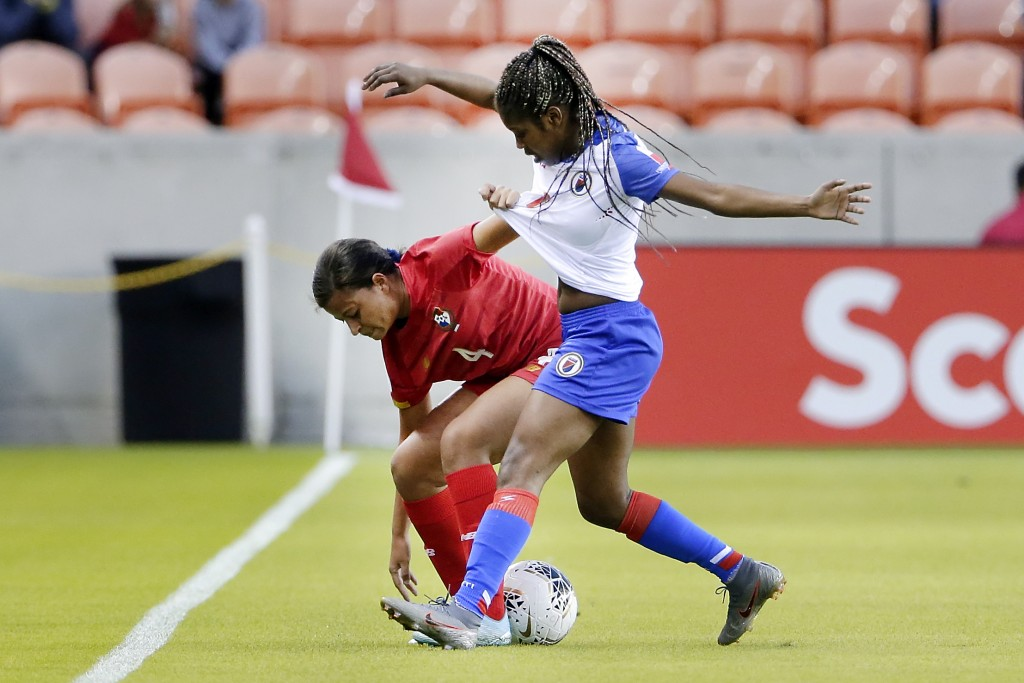 Panama defender Hilary Jaen (4) grabs the jersey of Haiti forward Batcheba Louis (7) as they battle for the ball during the first half of a CONCACAF w...