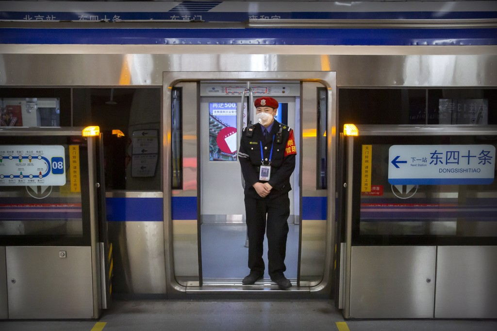 FILE - In this Feb. 3, 2020, file photo, a security officer wearing a face mask stands on a subway train in Beijing. Health authorities are preparing ...