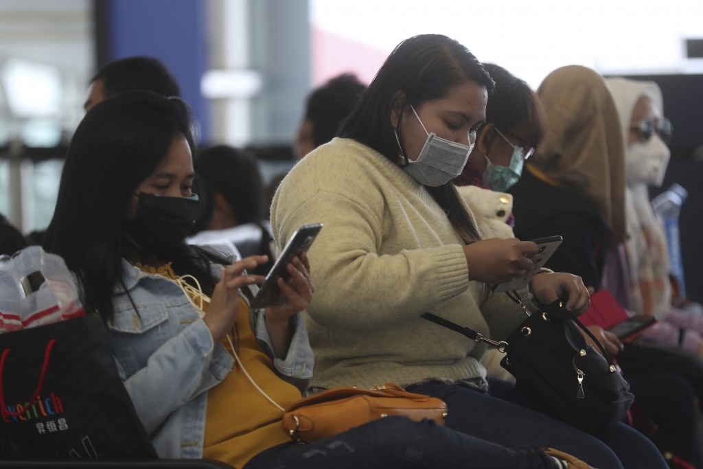 People wear masks at Hong Kong airport in Hong Kong, Tuesday, Feb. 4, 2020. (Hong Kong on Tuesday reported its first death from a new virus, a man who...