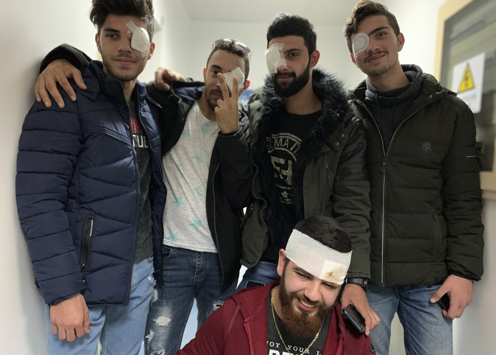 In this Jan. 27, 2020 photo, anti-government protesters, who were injured during clashing with riot police, pose for a group picture after a check up ...