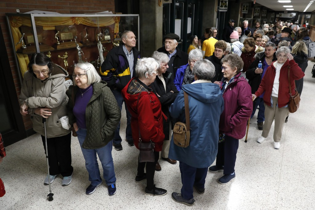 Local residents wait to enter an Iowa Democratic caucus at Hoover High School, Monday, Feb. 3, 2020, in Des Moines, Iowa. (AP Photo/Charlie Neibergall...