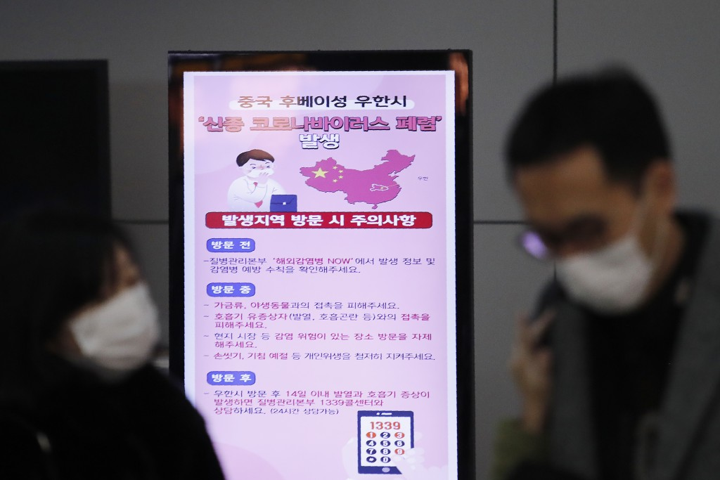 FILE - In this Jan. 27, 2020, file photo, a poster warning about coronavirus is seen as passengers wear masks in a departure lobby at Incheon Internat...