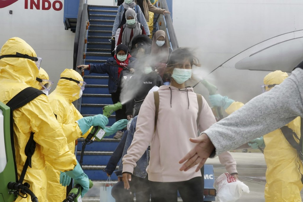 FILE - In this Sunday, Feb. 2, 2020, file photo released by the Indonesian Foreign Ministry, Indonesians who arrived from Wuhan, China, are sprayed wi...