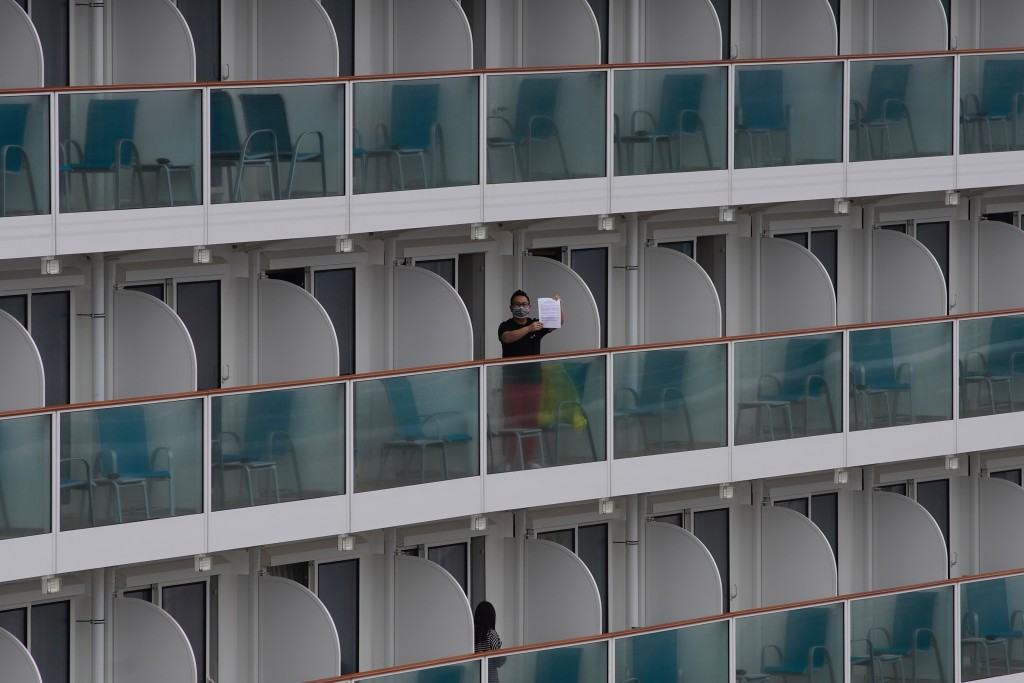 A passenger shows a note from the World Dream cruise ship docked at Kai Tak cruise terminal in Hong Kong, Wednesday, Feb. 5, 2020. A Hong Kong officia...