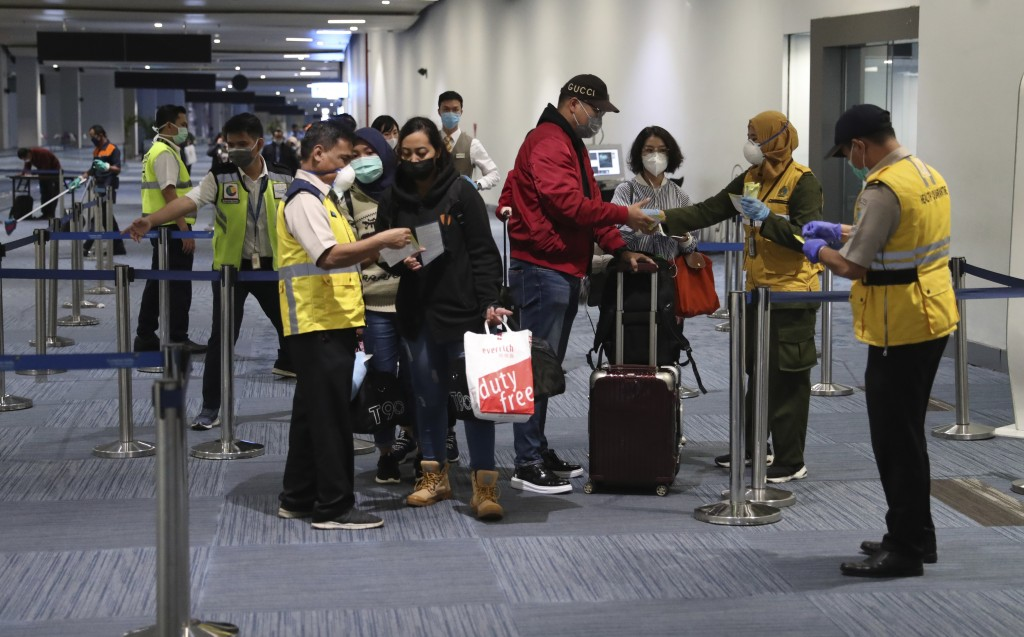 Officials check passengers arriving at Soekarno Hatta airport in Tangerang, Indonesia, Tuesday, Feb 4, 2020. (AP Photo/Achmad Ibrahim)