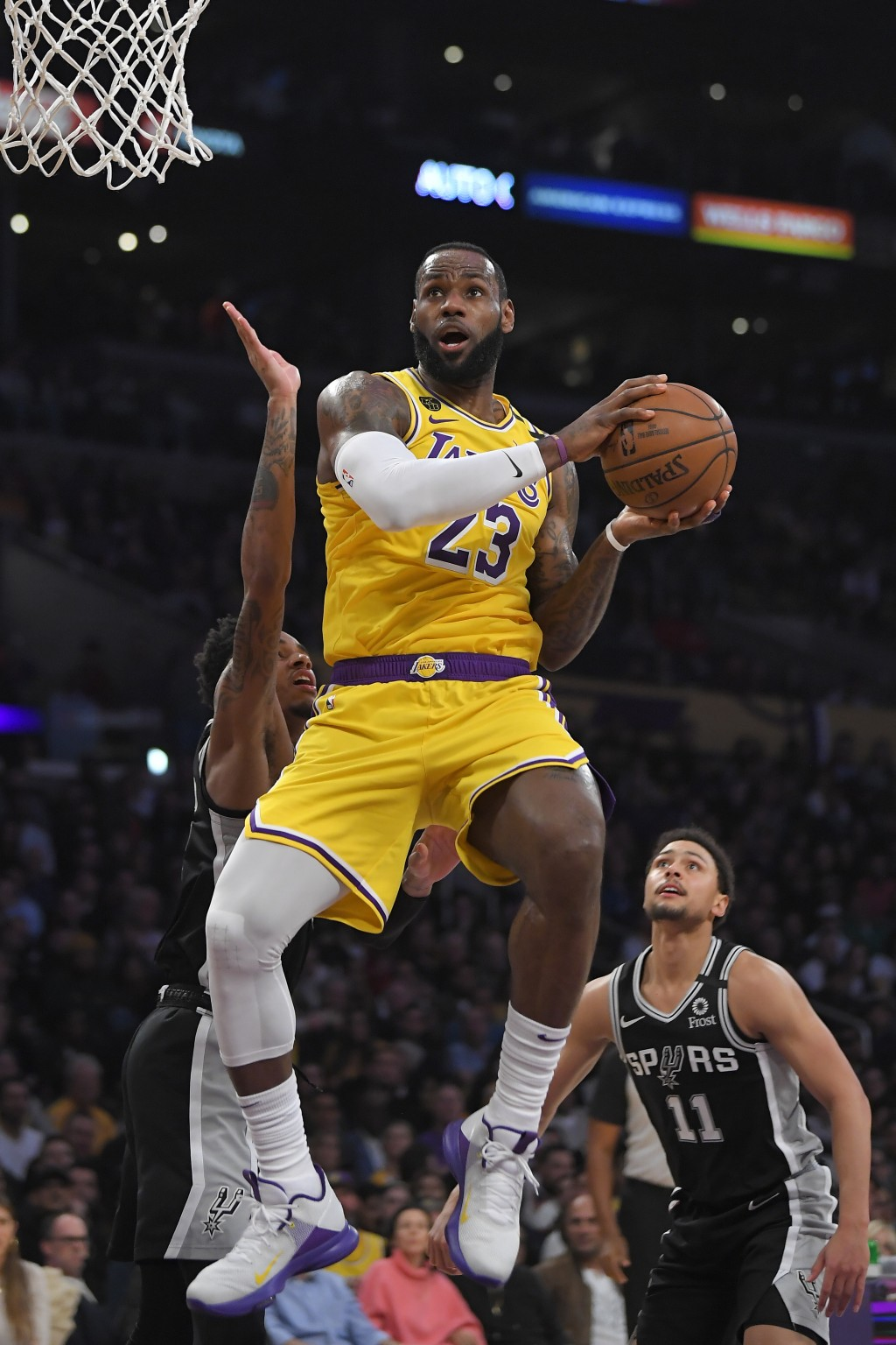 Los Angeles Lakers forward LeBron James, center, goes to the basket as San Antonio Spurs guard Dejounte Murray, left, and guard Bryn Forbes defend dur...