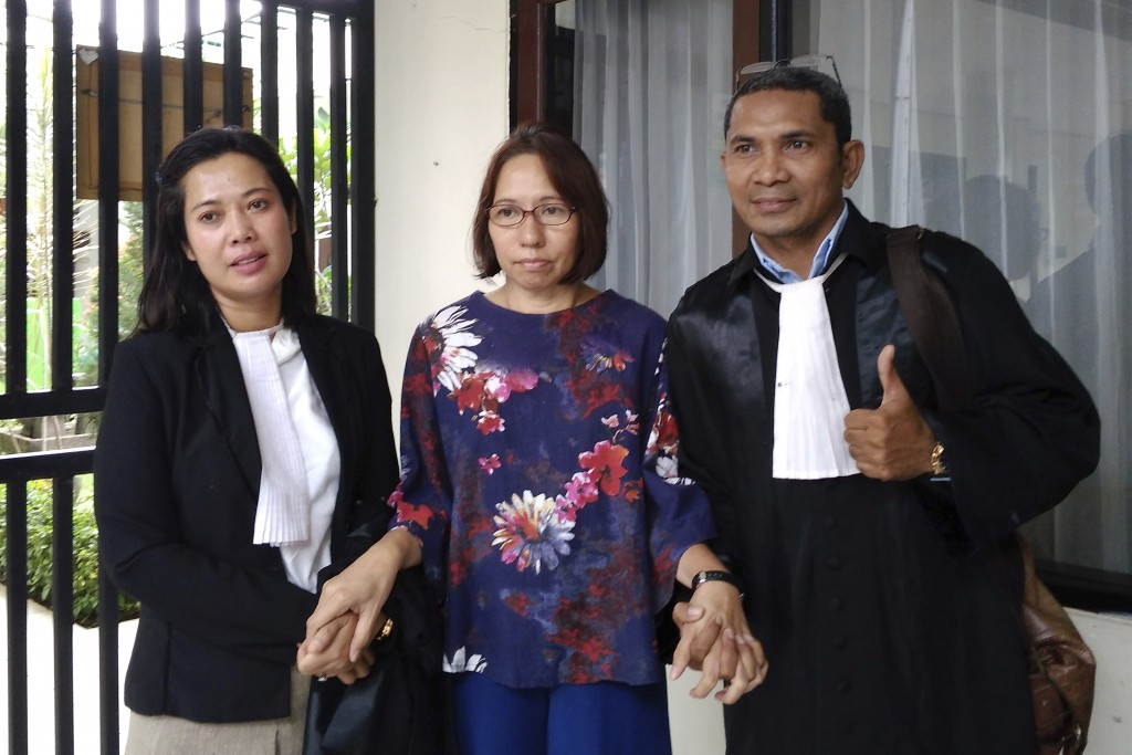 Suzethe Margareth, center, poses with her lawyers after her verdict at the Cibinong District Court in West Java, Indonesia, Wednesday, Feb. 5, 2020. D...