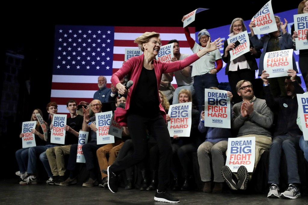 Democratic presidential candidate Sen. Elizabeth Warren, D-Mass., runs on stage as she greets a supporter, not shown, at the start of a campaign stop,...