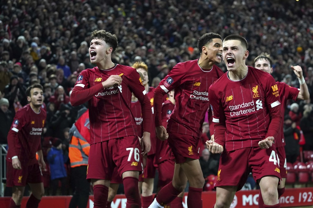 Liverpool players celebrate after Shrewsbury Town's Ro-Shaun Williams, scored an own goal during the English FA Cup Fourth Round replay soccer match b...