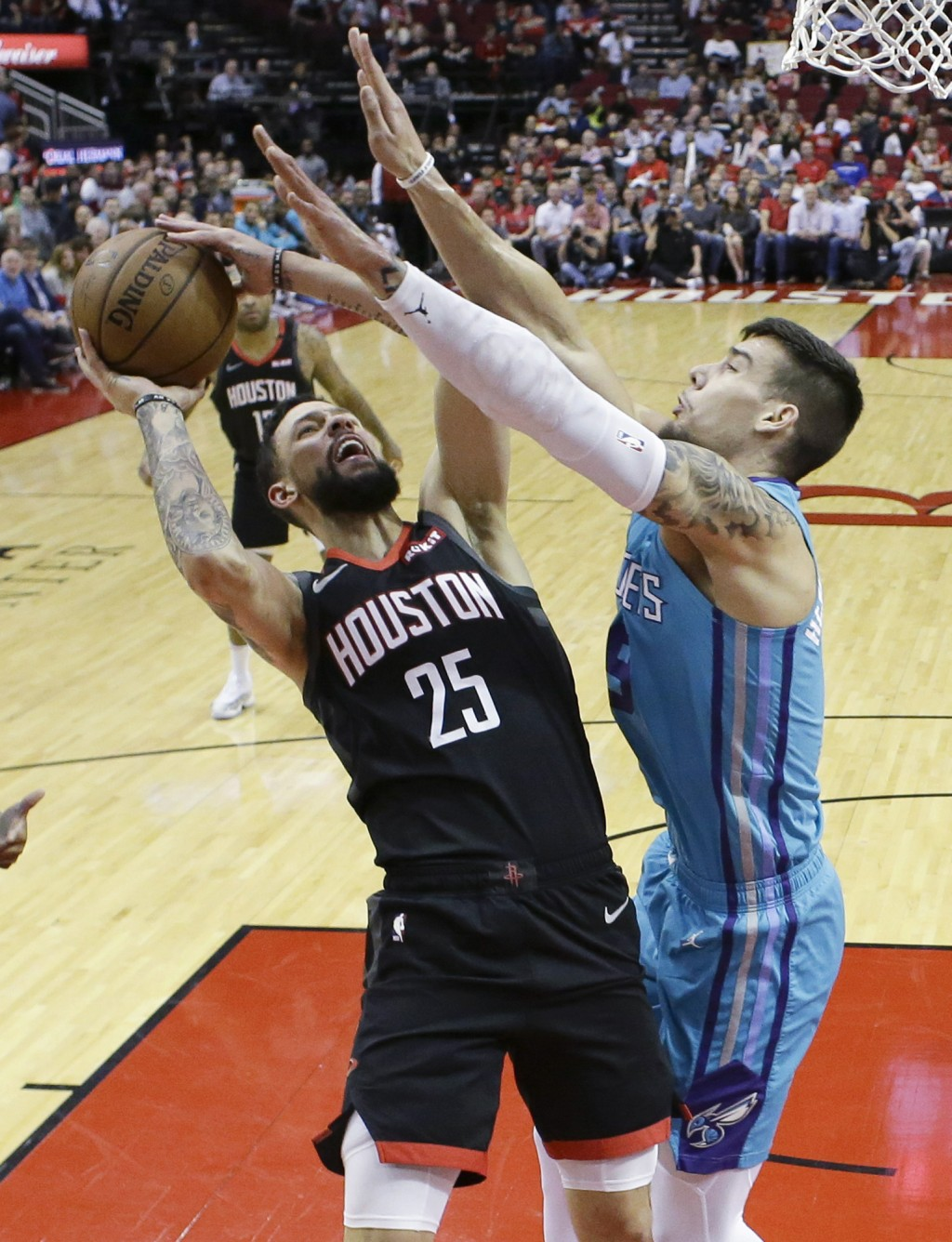 Houston Rockets guard Austin Rivers (25) shoots as Charlotte Hornets center Willy Hernangomez defends during the first half of an NBA basketball game ...