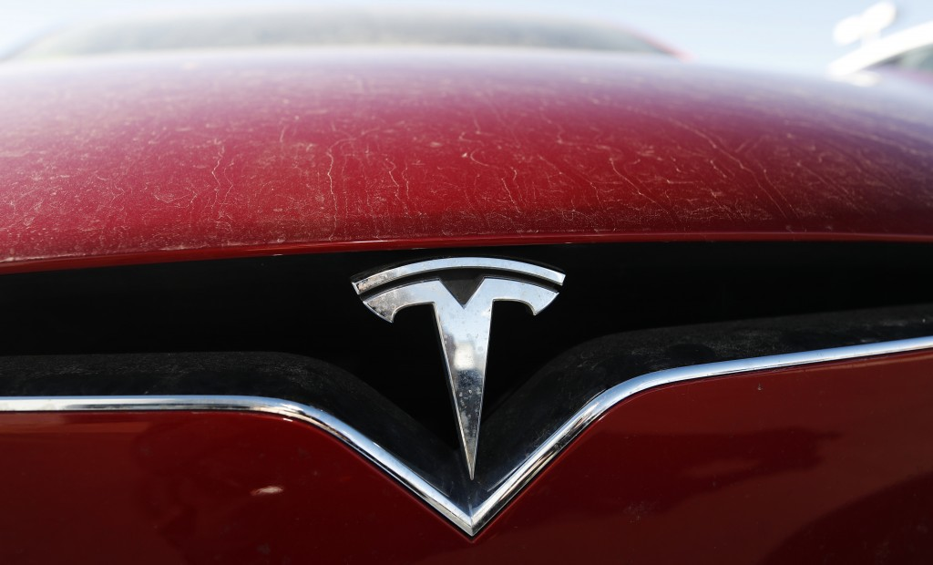 FILE - In this Feb. 2, 2020, file photo, the company logo shines on the grille of an unsold 2020 Model X at a Tesla dealership in Littleton, Colo. Tes...