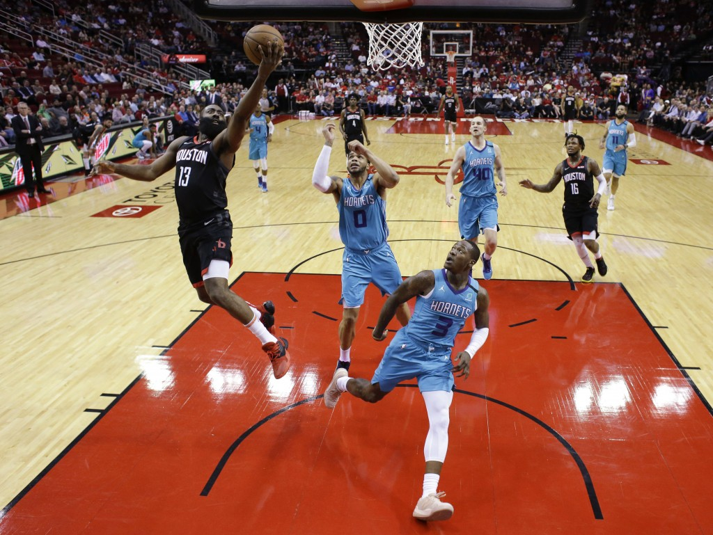 Houston Rockets guard James Harden (13) drives to the basket during the first half of the team's NBA basketball game against the Charlotte Hornets, Tu...