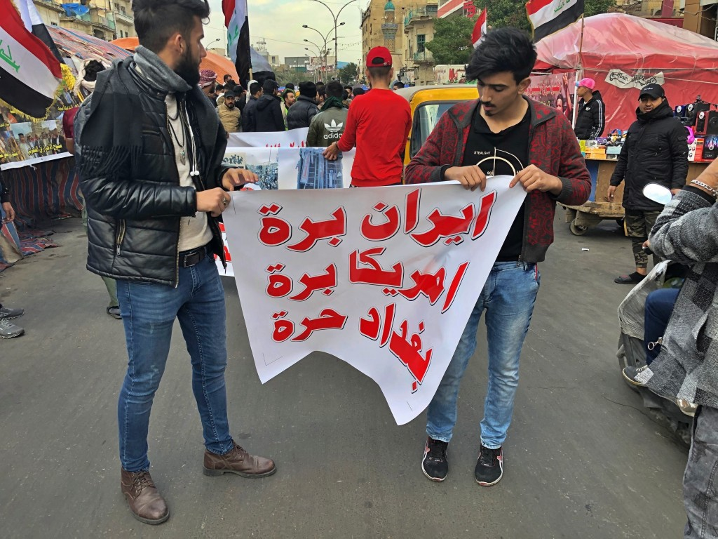 "FILE - In this Jan. 8, 2020 file photo, protesters hold a banner with Arabic that reads, ""Iran out, U.S. out, Baghdad is free"" during a sit-in at Tahr..."