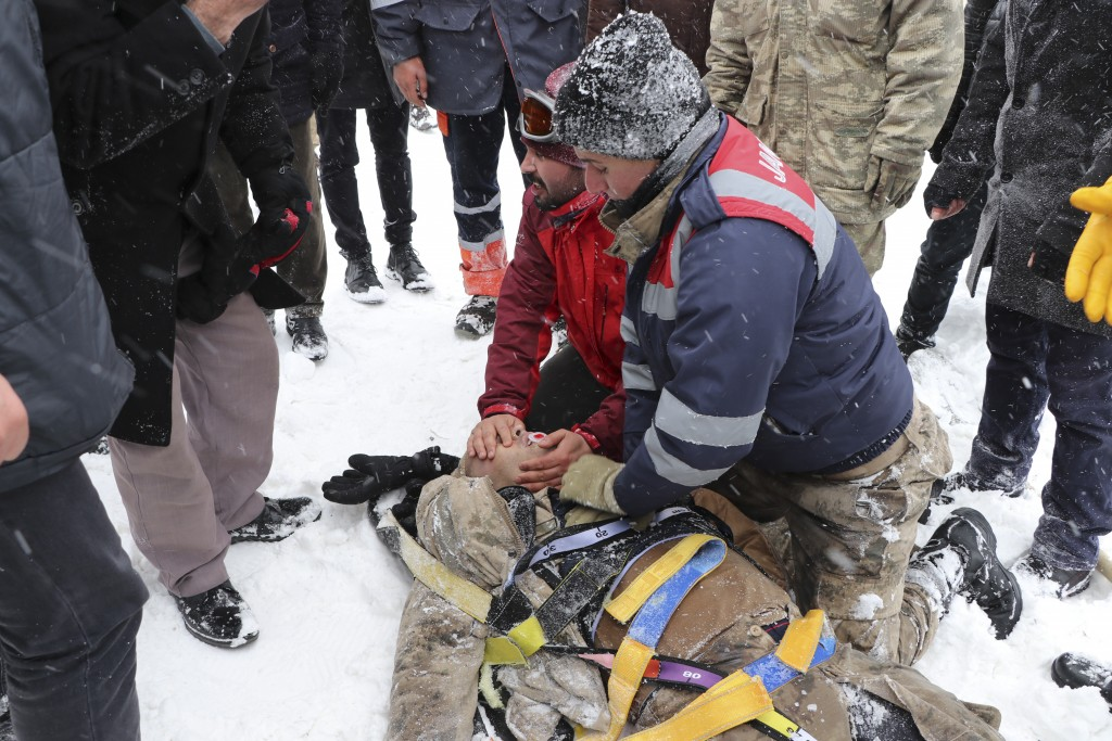 Emergency service members give first aid to victim of an avalanche, near the town of Bahcesaray, in Van province, eastern Turkey, Wednesday, Feb. 5, 2...