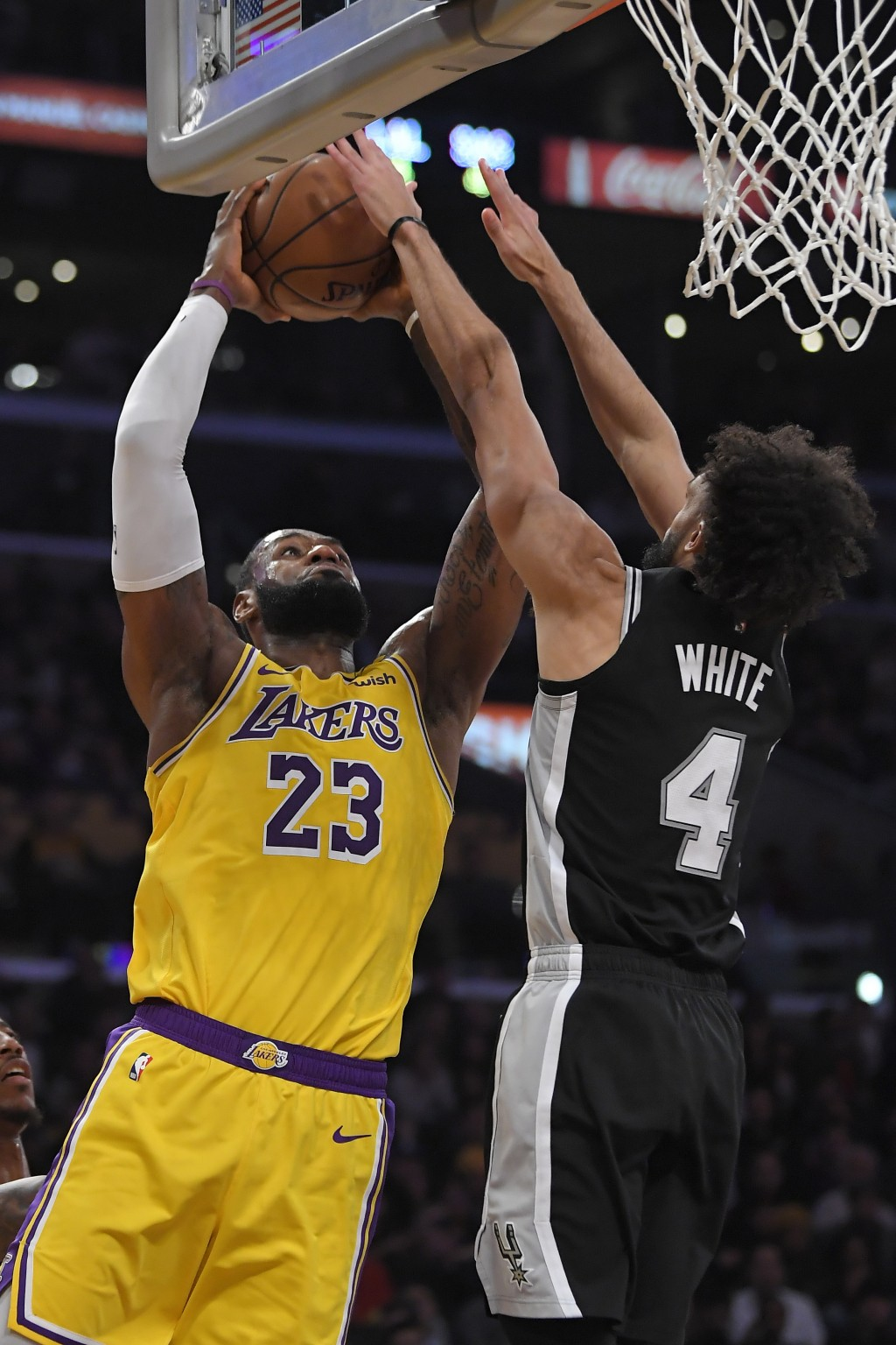 Los Angeles Lakers forward LeBron James, left, shoots as San Antonio Spurs guard Derrick White defends during the second half of an NBA basketball gam...