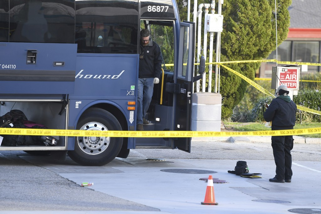 FILE - This Feb. 3, 2020 file photo shows investigators outside of a Greyhound bus after a passenger was killed on board in Lebec, Calif. Investigator...