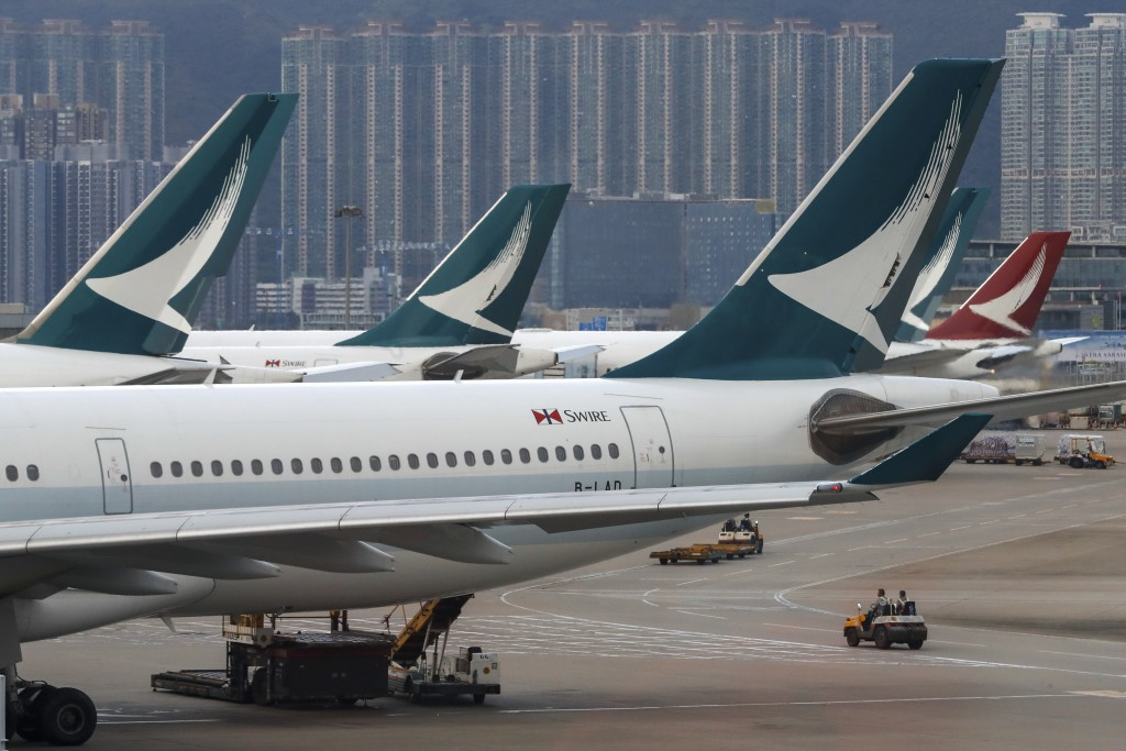 FILE - In this Aug. 12, 2019, file photo, ground crew drive past Cathay Pacific Airways planes park at the Hong Kong International Airport. Hong Kong ...