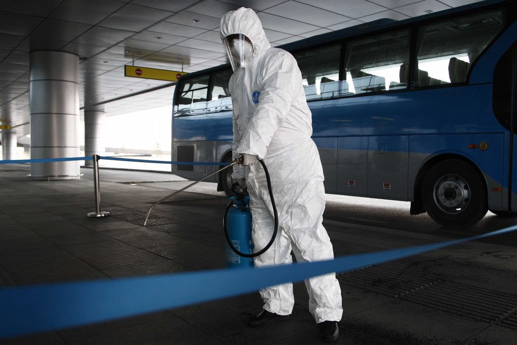 FILE - In this Feb. 1, 2020, file photo, State Commission of Quality Management staff in protective gear disinfects a ground transportation area at th...