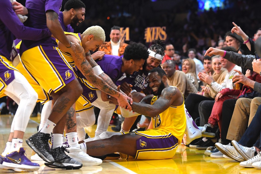 Los Angeles Lakers forward LeBron James I swarmed by teammates after making several 3-point shots in a row during the second half of the team's NBA ba...