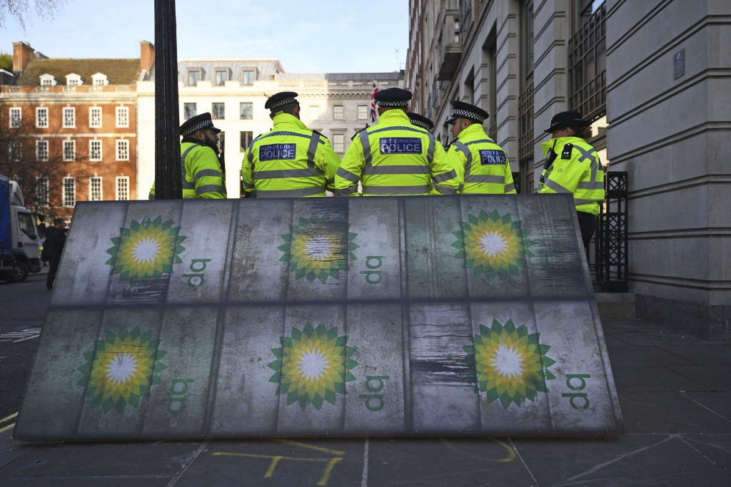 Police officers stand near activists outside BP's headquarters to mark the first day of the oil company's new chief executive Bernard Looney, at St Ja...