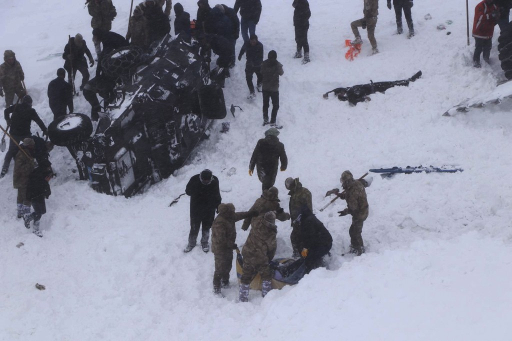 Emergency service members dig in the snow around at least three overturned vehicles, near the town of Bahcesehir, in Van province, eastern Turkey, Wed...