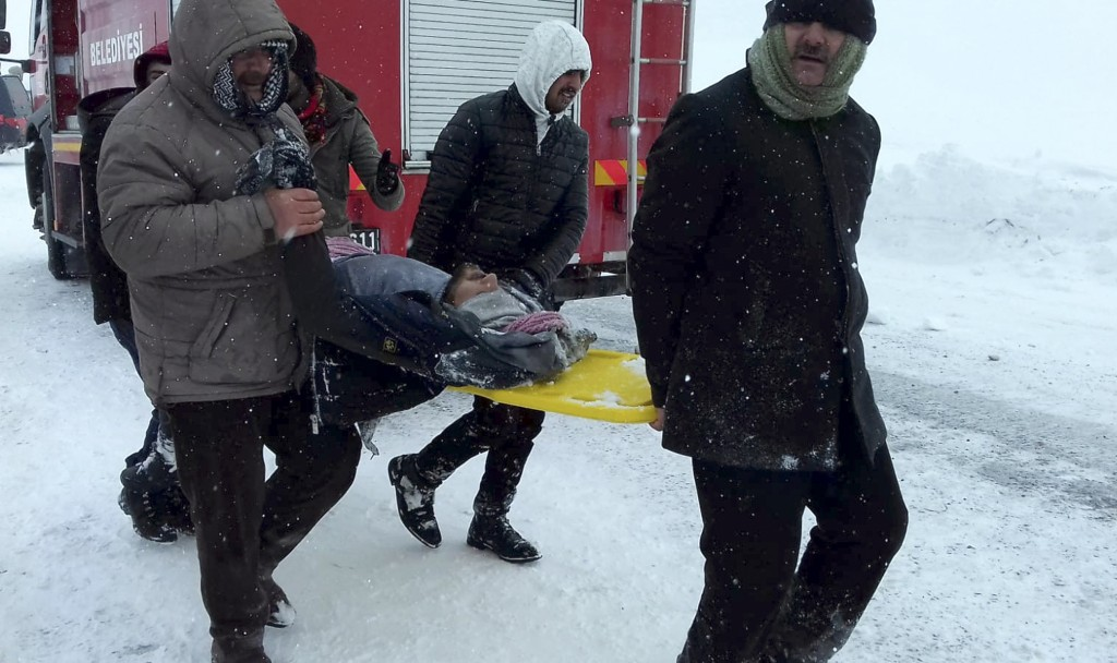Emergency service members carry a casualty at the site of avalanche near the town of Bahcesehir, in Van province, eastern Turkey, Wednesday, Feb. 5, 2...