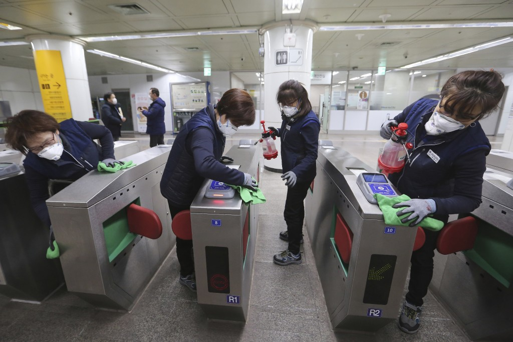 FILE - In this Jan. 28, 2020, file photo, employees disinfect ticket gates in hopes to prevent the contraction of the coronavirus at a subway station ...