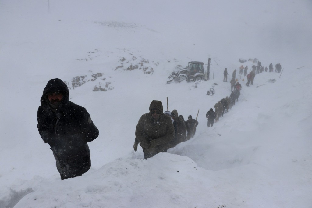 Emergency service members work in the snow around overturned vehicles, near the town of Bahcesehir, in Van province, eastern Turkey, Wednesday, Feb. 5...