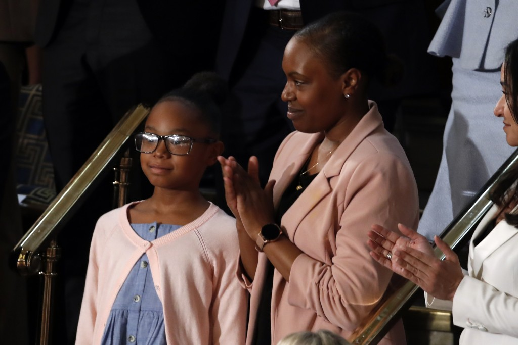 Janiyah, left, and Stephanie Davis of Philadelphia, listen as President Donald Trump delivers his State of the Union address to a joint session of Con...