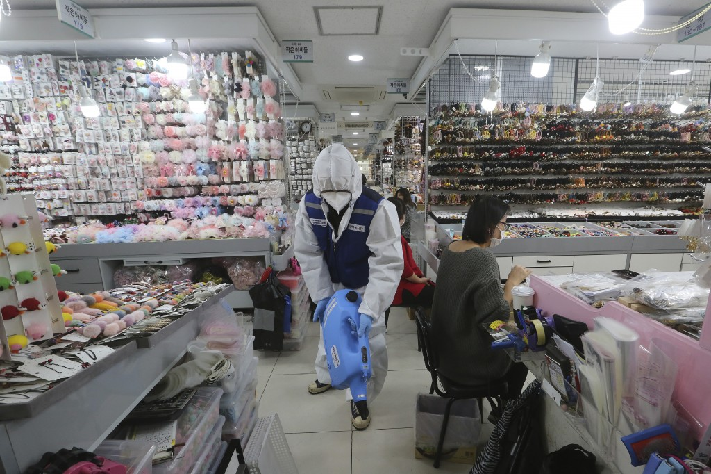 A worker wearing protective gears sprays disinfectant inside a store as a precaution against a new coronavirus at Namdaemun Market in Seoul, South Kor...