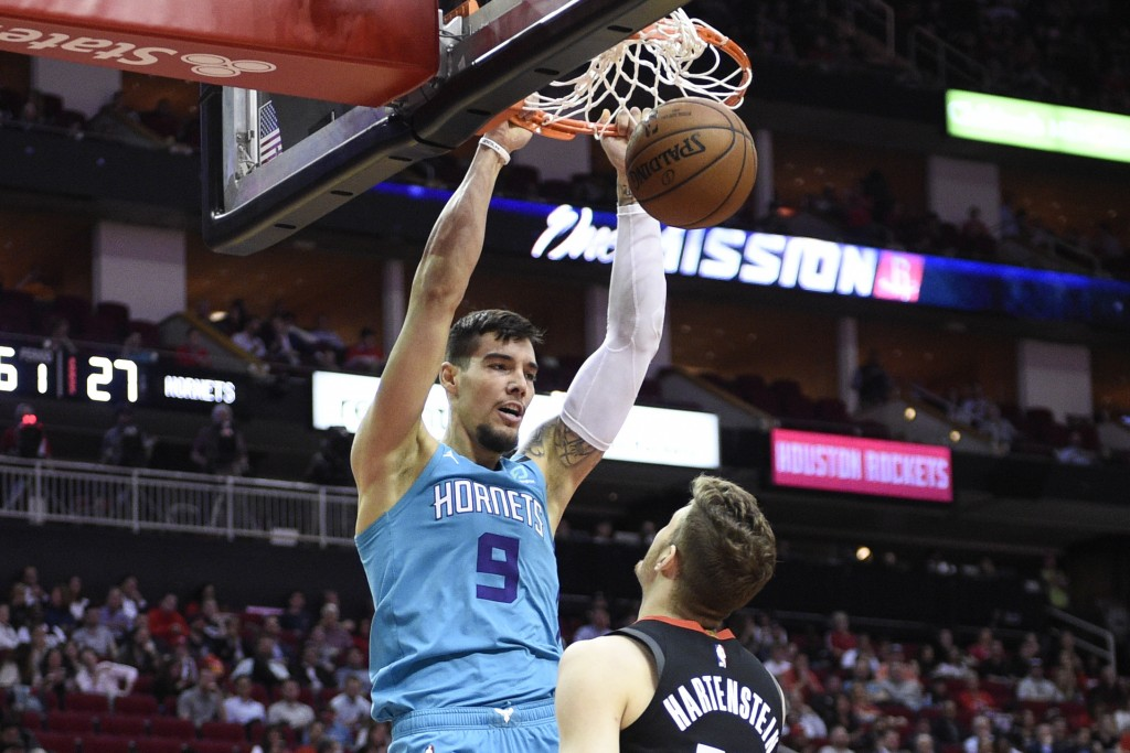 Charlotte Hornets center Willy Hernangomez (9) dunks in front of Houston Rockets center Isaiah Hartenstein during the first half of an NBA basketball ...