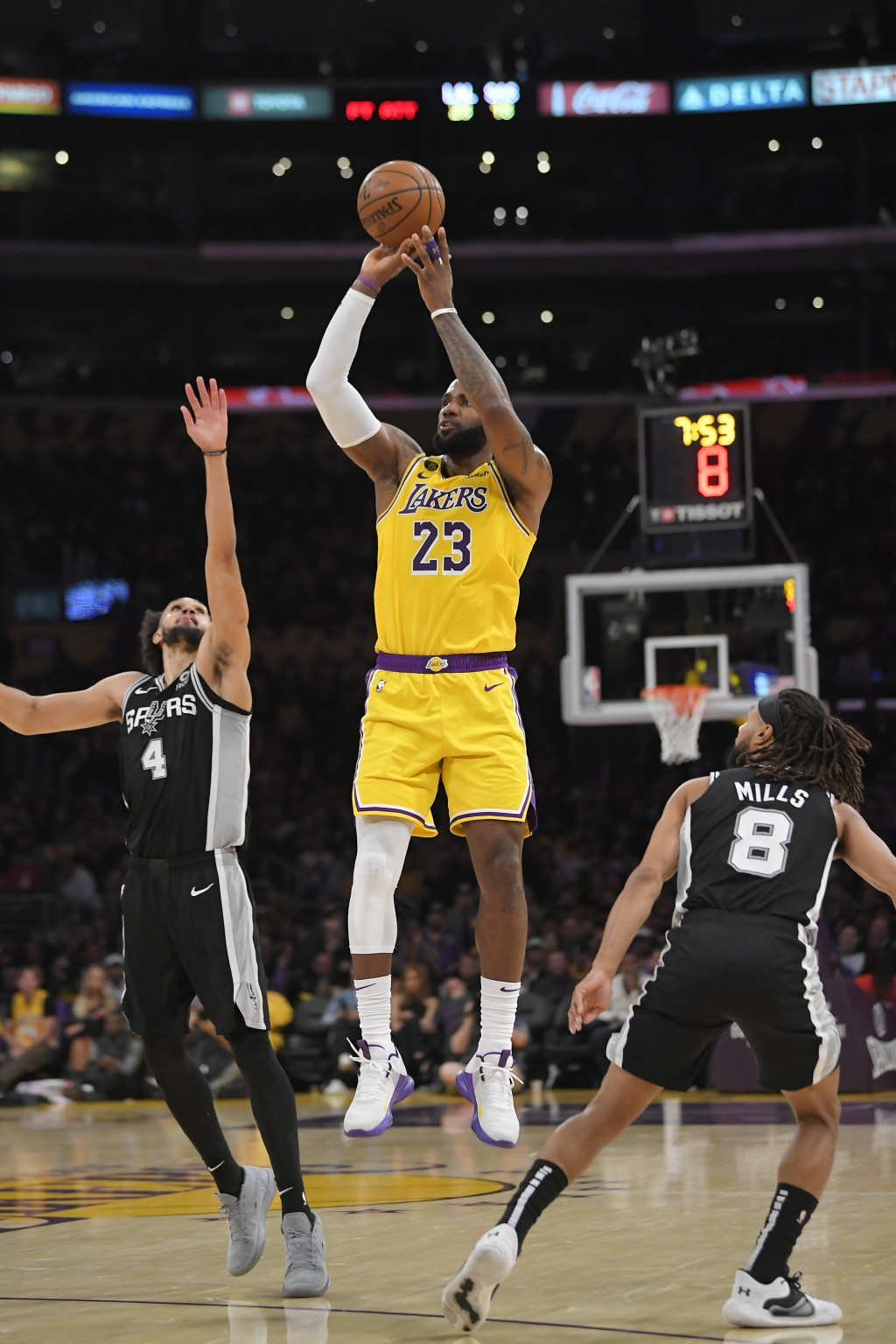 Los Angeles Lakers forward LeBron James, center, shoots as San Antonio Spurs guard Derrick White, left, and guard Patty Mills defend during the second...