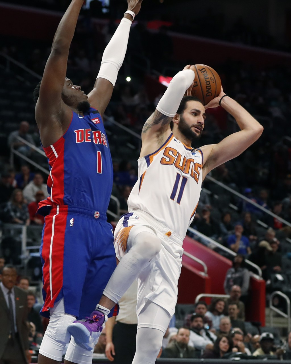 Phoenix Suns guard Ricky Rubio (11) passes as Detroit Pistons guard Reggie Jackson (1) defends during the first half of an NBA basketball game, Wednes...