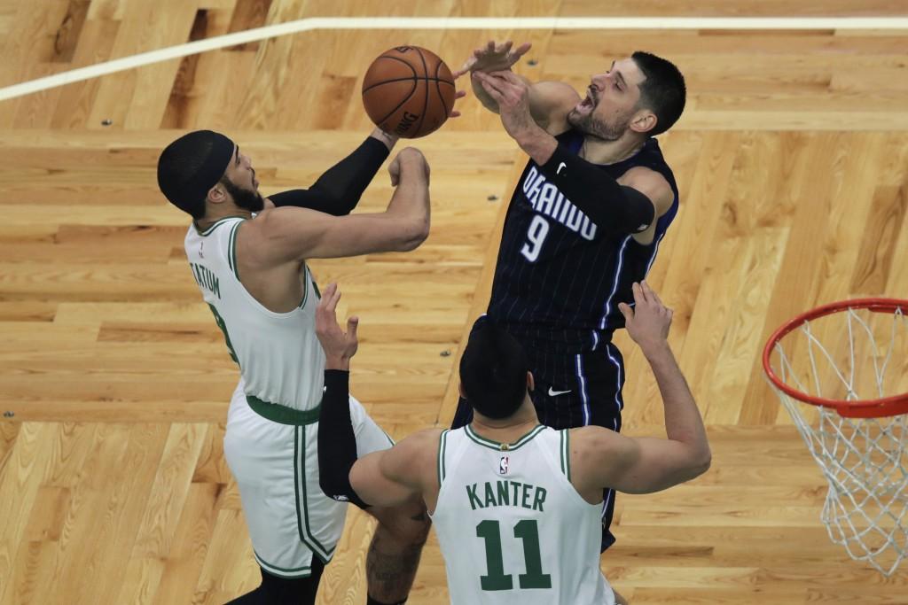 Orlando Magic center Nikola Vucevic (9) and Boston Celtics forward Jayson Tatum (0) vie for a rebound during the first quarter of an NBA basketball ga...