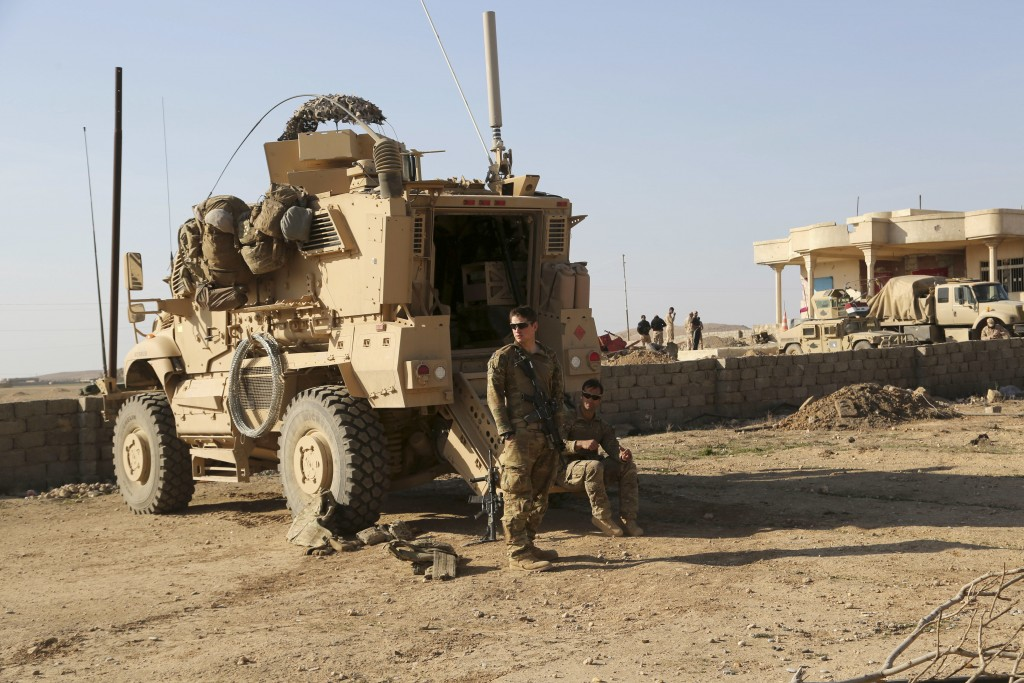 FILE - In this Feb. 23, 2017 file photo, U.S. Army soldiers stand outside their armored vehicle on a joint base with the Iraqi army, south of Mosul, I...