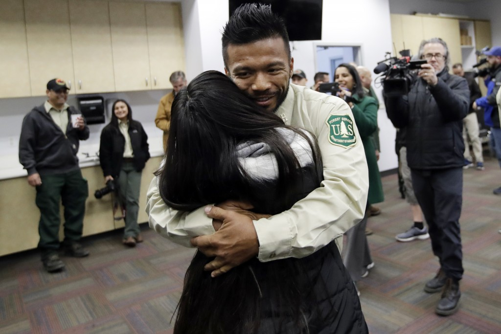 Firefighter Leonard Dimaculangan, of Pasadena, Calif. hugs his daughter Promise, 11, after arriving from a deployment fighting wildfires in Australia ...