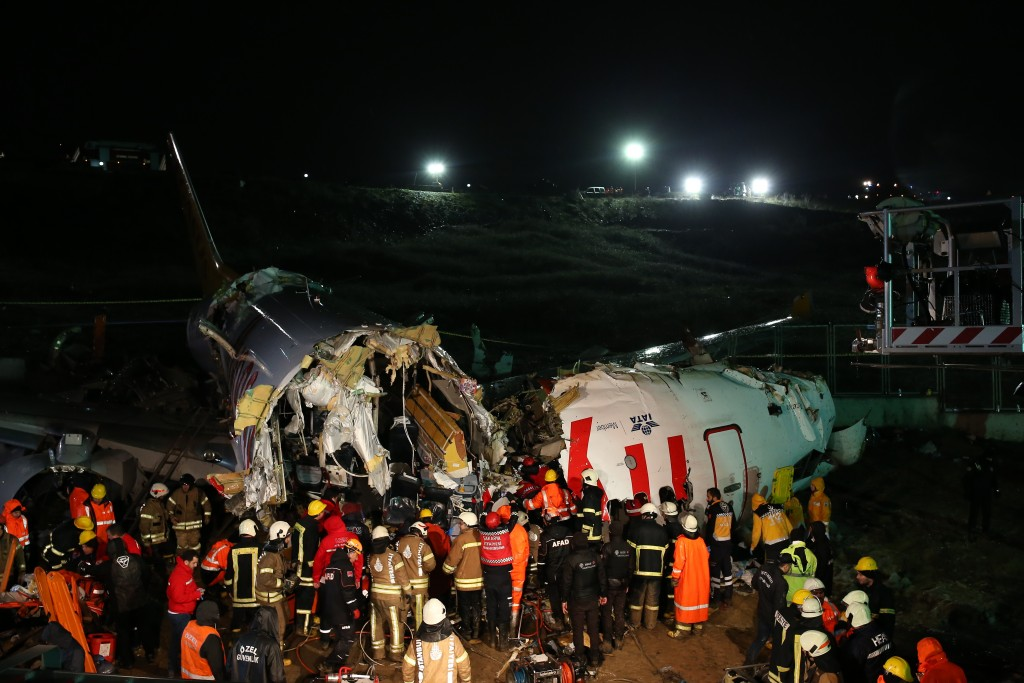 Rescue members and firefighters work around the wreckage of a plane after it skidded off the runway at Istanbul's Sabiha Gokcen Airport, in Istanbul, ...