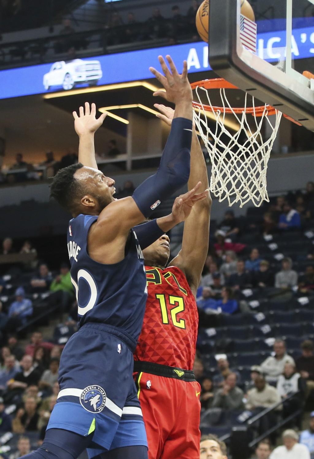 Minnesota Timberwolves' Josh Okogie, left, of Nigeria, shoots as Atlanta Hawks' De'Andre Hunter defends in the first half of an NBA basketball game We...