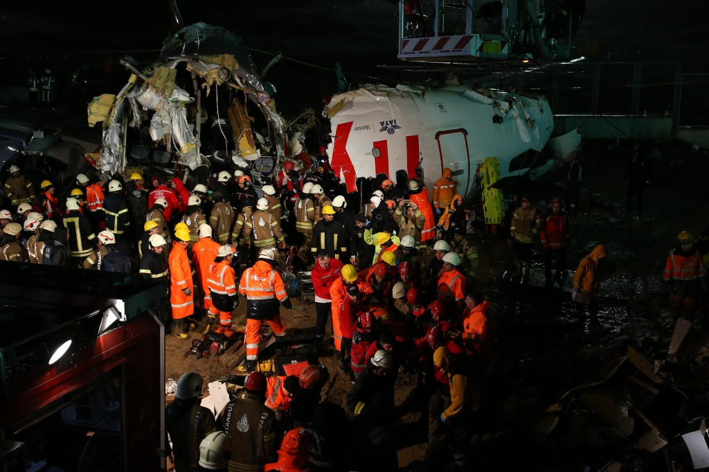 Rescue members, centre bottom, evacuate an injured person from the wreckage of a plane after it skidded off the runway at Istanbul's Sabiha Gokcen Air...