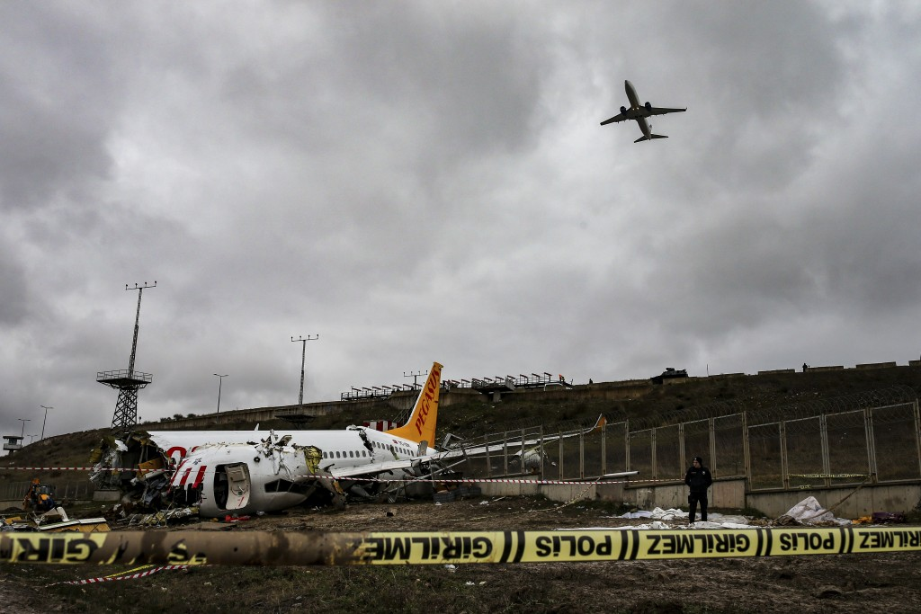 A plane takes off as Turkish police guard the wreckage of a plane operated by Pegasus Airlines after it skidded Wednesday off the runway at Istanbul's...