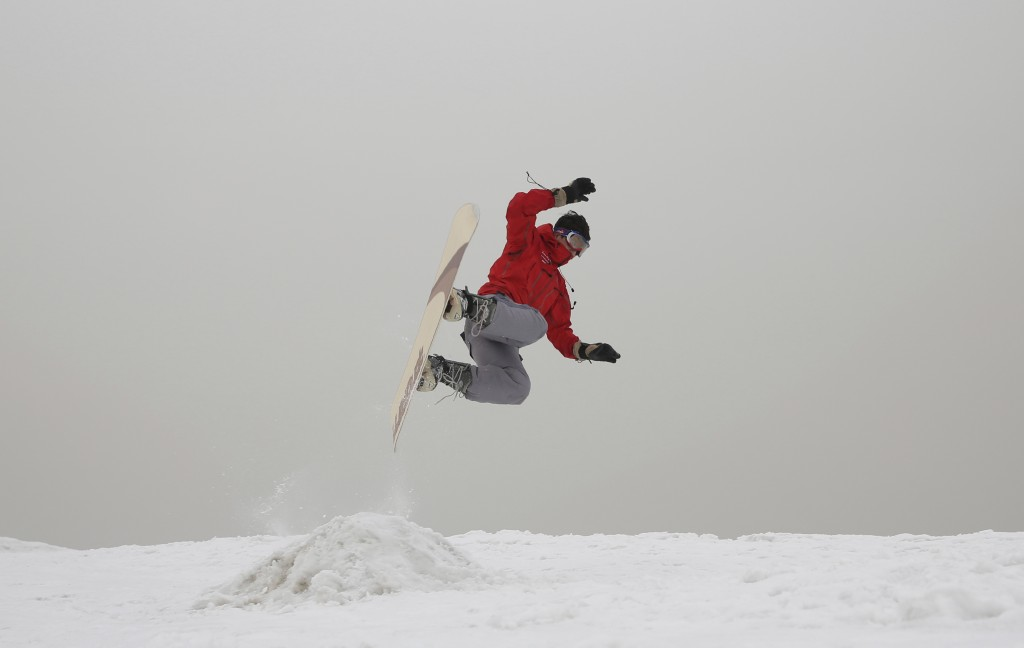 In this Friday, Jan. 24, 2020 photo, Mohammad Farzad, 20, a member of the Afghanistan Snowboarding Federation practices on the hillside known as Kohe ...