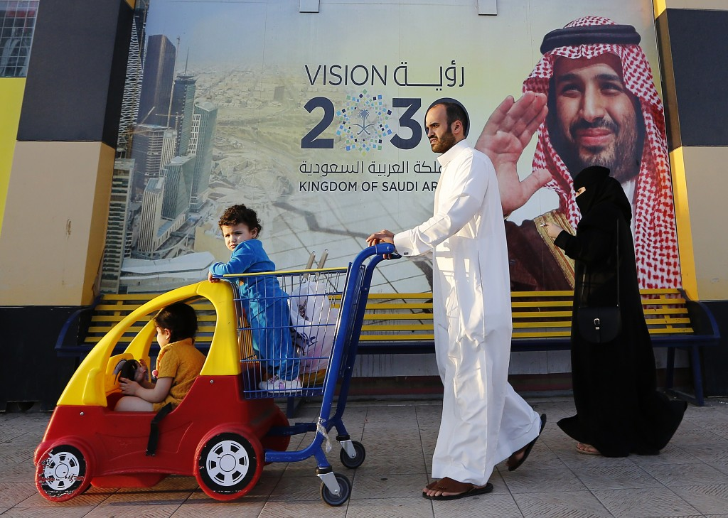 In this Wednesday, Feb. 5, 2020, photo, people walk past a banner showing Saudi Crown Prince Mohammed bin Salman, outside a mall in Jiddah, Saudi Arab...