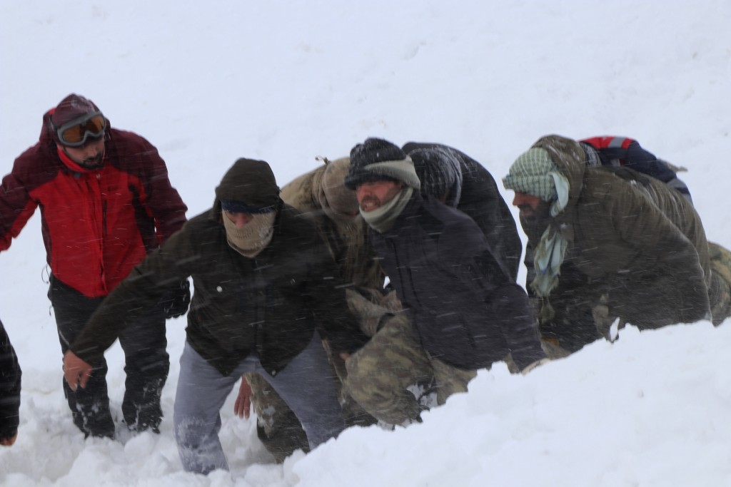 Emergency service members carry a victim of an avalanche, near the town of Bahcesaray, in Van province, eastern Turkey, Wednesday, Feb. 5, 2020. An av...