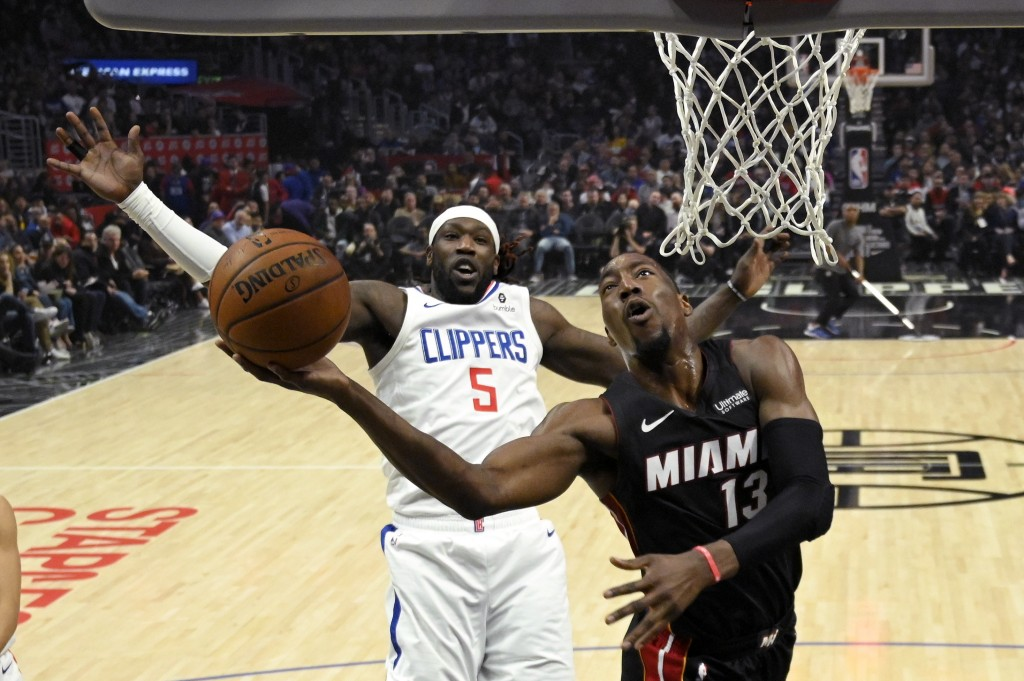 Miami Heat forward Bam Adebayo, right, shoots as Los Angeles Clippers forward Montrezl Harrell defends during the first half of an NBA basketball game...