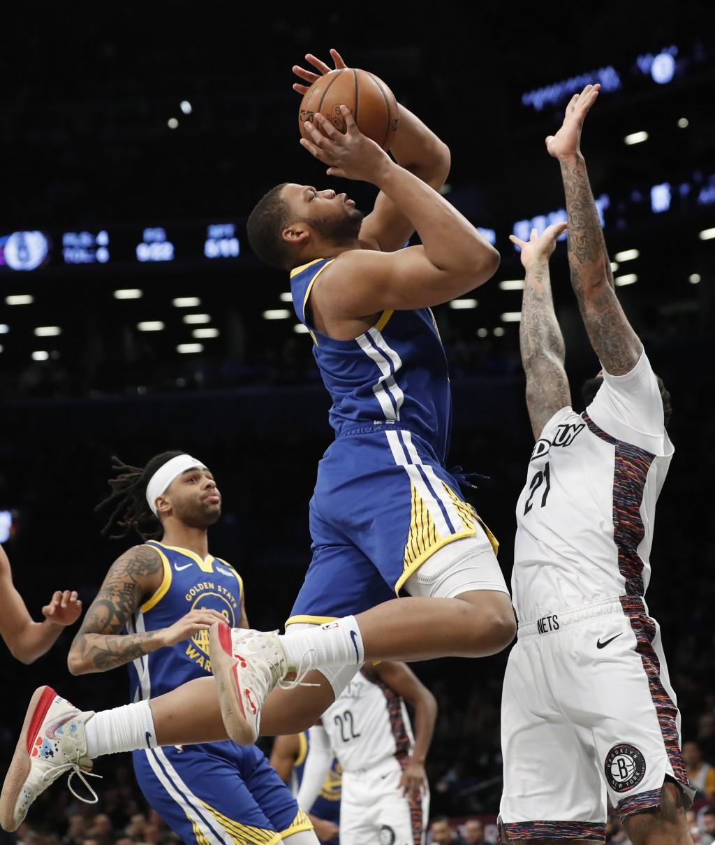 Golden State Warriors forward Omari Spellman (4) shoots as Brooklyn Nets forward Wilson Chandler (21) defends during the first half of an NBA basketba...