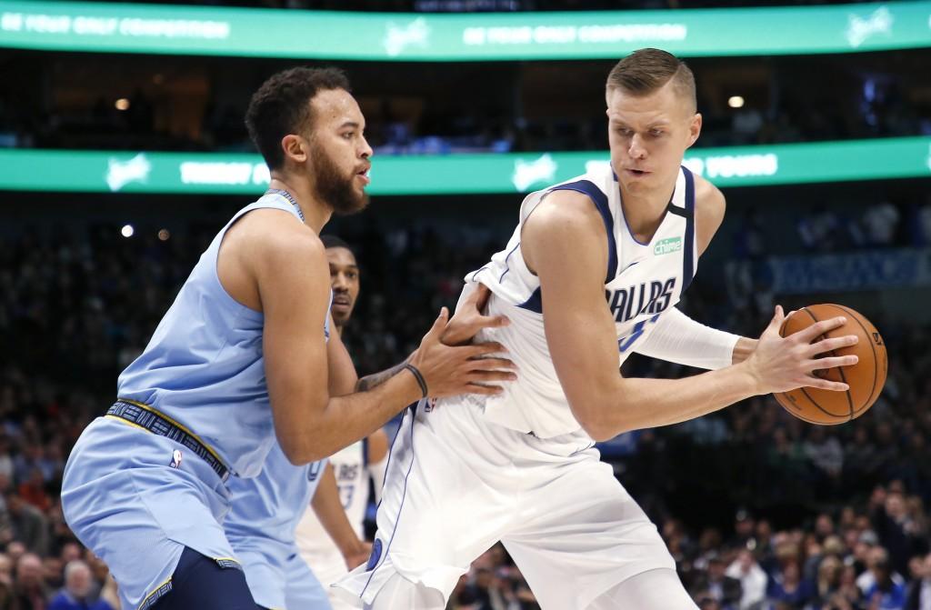 Dallas Mavericks forward Kristaps Porzingis (6) looks inside as Memphis Grizzlies forward Kyle Anderson (1) defends during the first half of an NBA ba...