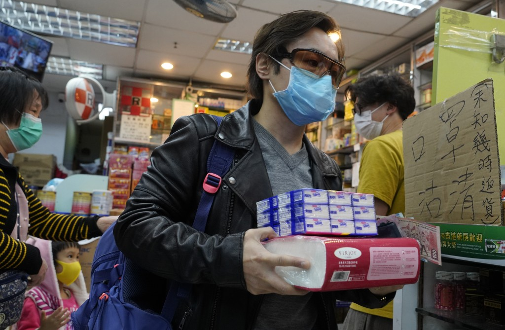 A man wearing a protective face mask carries purchased tissue papers at a pharmacy in Hong Kong, Thursday, Feb. 6, 2020. Ten more people were sickened...
